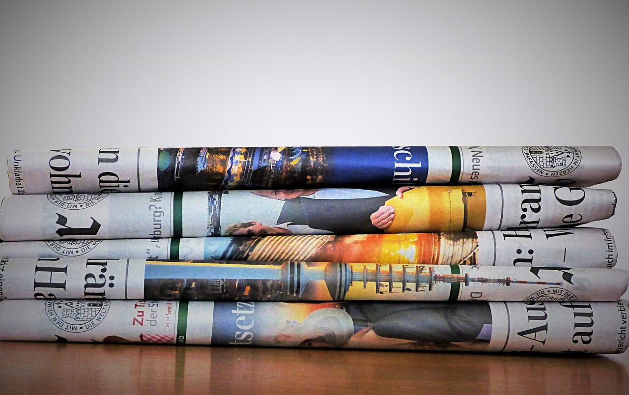 A stack of folded newspapers with colourful images.